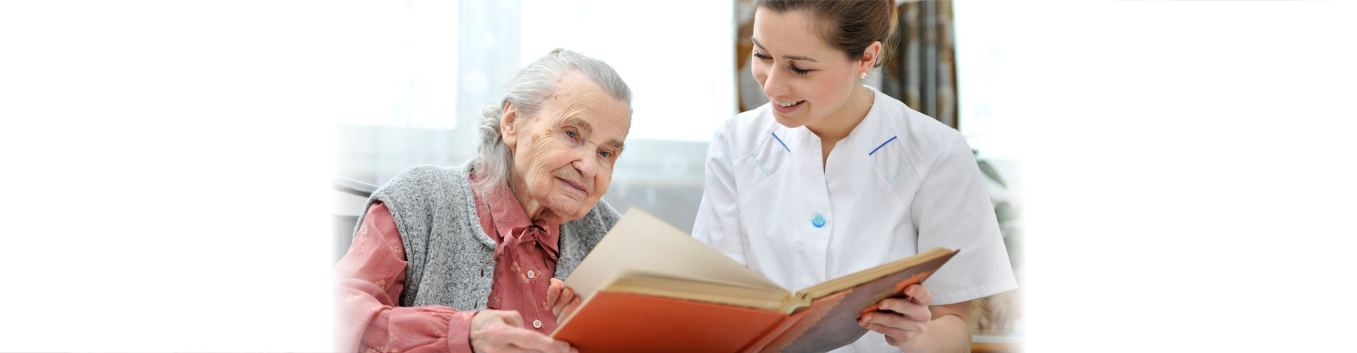 caregiver and elderly woman reading book
